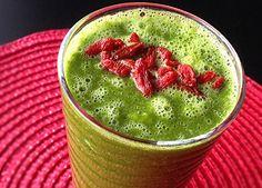 vackert grön smoothie toppad med gojibär röd duk