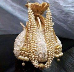 Designed with the heart, this beautiful Potli or batawa bag with eye catchy handle and used premium row silk material. This potli having light embroidery of flowers with pearls border at outer side. Bridal Clutch, Wedding Clutch, Wedding Bag, Pearl Necklace Designs, Potli Bags, Designer Clutch, Indian Party, Trendy Collection, Beaded Bags