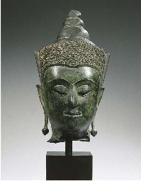 a thai, ayutthaya style, bronze head of buddha shakyamuni  early 16th century  His face with serene expression, arched eyebrows above incised eyes, aquiline nose, smiling lips, elongated earlobes with pendeloque ear rings, tiara moulded with scrolling flowers and a conical shaped usnisha, traces of green patina 32 cm high, mounted