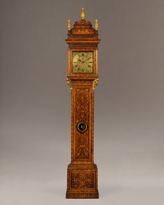 CLAUDIUS DU CHESNE An exceptional Queen Anne period walnut and marquetry longcase clock of month duration with square dial and original caddy top by this well-known maker. The case is veneered with highly decorative foliate marquetry scrolls and exotic birds. The elegant long trunk door with its brass moulded glass lenticle is surmounted by two original carved gilt wood trusses. All the crossgrain mouldings and hood pillars are in patinated walnut.