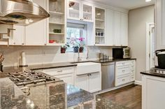 Contemporary Kitchen with Hardwood floors, Glass panel door, L-shaped, Farmhouse sink, Glass panel, Subway Tile, Flush