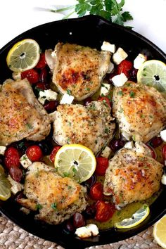 Top view of a cast iron skillet filled with Greek Lemon Oven Roasted Chicken Thighs with tomatoes, Kalamatas, Feta cheese and lemon slices.