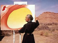 Georgia O'Keeffe adjusts a canvas from her Pelvis Series- Red With Yellow in Albuquerque, New Mexico