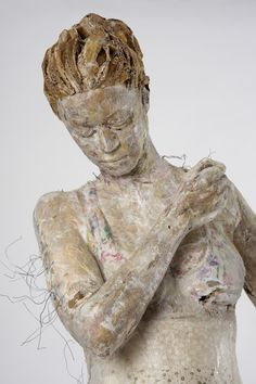Greek artist Vally Nomidou creates life sized sculptures of human figures using nothing but paper and card board. The internal frame is built with cardboard with vertical and horizontal grid in order to give support to the structure. The outer skin is finished off with newspaper, paper towels, handmade paper and other materials salvaged from around the house, cut, sewn, glued and rubbed to achieve the realistic rendering of her subjects. Apparently, she also uses partial plaster casts.
