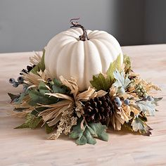 Spice up your table for the harvest season with this White Pumpkin and Leaves Arrangement! Its natural design makes it the perfect finishing touch for fall.             Overall centerpiece measures 14L x 14W x 9H in.          Crafted of artificial materials          Leaf, pine cone, berry, and pumpkin mix          Hues of blue, green, white, and brown          For decorative use only          Care: Dust with a soft, dry cloth.          Contact your local Kirkland's store for availability. Quanti