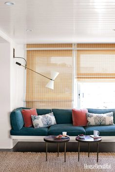 A window seat in the living room is upholstered in Pacific Blue Lido chenille from Dunham's textile line. Unlined natural woven shades filter the light. The 1950s French wall lamp is by Pierre Guariche.
