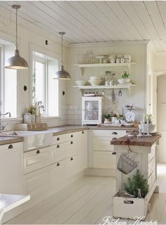WHITE KITCHEN THAT IS WARM because of the added wood. A bit too much white. Would anchor it w/wood flooring.