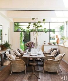 DeGeneres and De Rossi's Beverly Hills Estate.  They added a screened porch, where a 19th-century trestle table is paired with wicker armchairs.