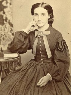 Bow and sleeve trim. Silk dress. Note the size and length of the bow which appears to be not tied in a knot but held in place with a small broach, the buttons and spacing on the dress as well as they appear to be shell, the belt.