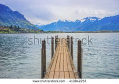 A wooden pier in lake Geneva, Montreux, Switzerland. A view from Chateau de Chillon (Chillion castle) with snow moutain in background. - stock photo