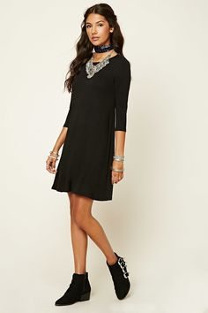 - A stretch-knit mini dress featuring a swingy silhouette, a round neckline, and 3/4 sleeves.