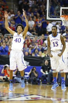 Kansas players Kevin Young, left, and Elijah Johnson celebrate a dunk by teammate Ben McLemore ...Big 12 tournament
