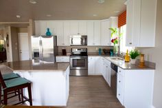 Model home kitchen with white cabinets, stainless steel appliances and granite