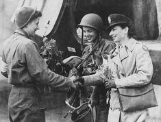 Second Lt Suella Bernard shakes hands with Lt Foster, the head nurse. These two women are the first nurses to go on the Ninth Air Force evacuation mission to Normandy, and first to return with wounded to England.