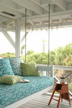 Turquoise floral print cushions on a comfy porch swing at a beach house. #porch #beachhouse