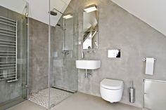 OOOOX | CESKE DRUZINY - attic bathroom with grey cement walls and river stone mosaic
