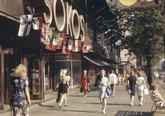1971 . Jalankulkijoita Mannerheimintiellä Sokoksen tavaratalon kohdalla. Eri maiden lippuja. Mannerheimintie 9.