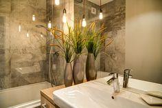 Minimalistyczne wnętrze łazienki z płytkami imitującymi beton. Oświetlenie  w postaci zwisających żarówek, które odbijają się w dużym lustrze powiększają przestrzeń i nadają jej klimatu, mimo tej surowości. Sink, Bathtub, Bathroom, Home Decor, Sink Tops, Standing Bath, Washroom, Vessel Sink, Bathtubs