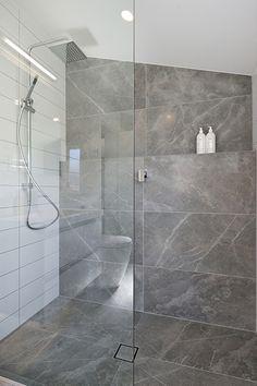 Bathroom: Grey Fluery 450 x 900. Designer: John Kaminski - Bathroom Direct https://www.tiles.co.nz/About/News/ArticleID/70/Freemans-Bay-Home-with-beautiful-honed-tiles
