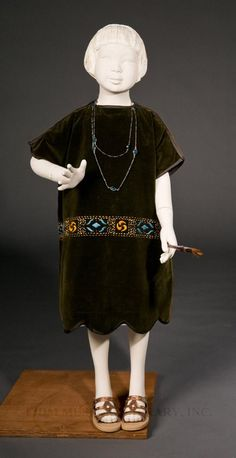 The low waistline on this girl's dress from around 1913 is typical of the time. Girls' dresses are noted by their shorter lengths.