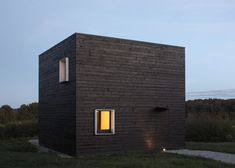 Black-painted timber contrasts with clean white window frames on the walls of this cube-shaped weekend home in Normandy, France
