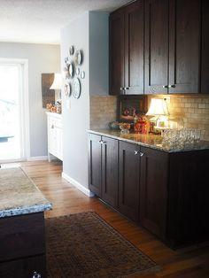 Dark cabinets, glass knobs, light backsplash, pale blue walls. Just what I want!