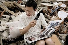 man cries as he flips through a family album he found in the rubble of his old house following an earthquake in Sichuan