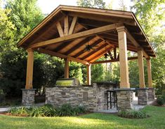 This custom outdoor structure is a great place for entertaining guests. A full outdoor kitchen is surrounding by a natural stone façade. The stone column bases with bluestone caps are beautifully complemented by the gorgeous wood framing above.