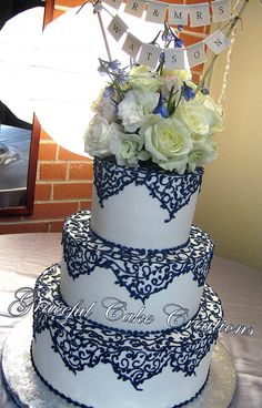 Elegant Ivory Wedding Cake with Navy Blue Lace. LOVE the lace overlay in Navy! overdone flowers on top for my taste.