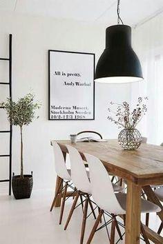 Sala de Jantar com cadeiras brancas Eames e mesa de madeira retangular.