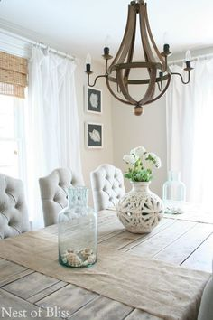 White floor-length curtains in coastal dining room