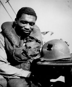 Marine Corps Coast Guardsman Charles Tyner, Fireman first class, examines the jagged shrapnel hole in the helmet he wore during the initial assault on the beaches of Southern France Tyner suffered just a superficial scratch.