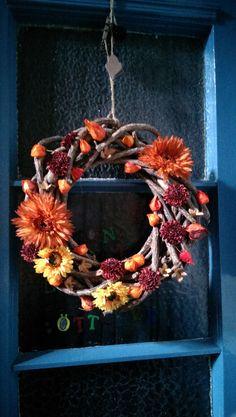 Holzkranz verziert mit Kunstblumen, Lampionfrüchten aus dem Garten und was einem sonst noch so in die Hände fällt an Herbstdeko. Habe hier Resteverwertung gemacht und finde, es kann sich sehen lassen :)