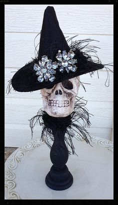 Halloween decoration A cute skull is wearing a felt witch hat with eyelash trim and two large rhinestone buttons The skull is attached to a candlestick and has a matching collar. wicked 12inches high Halloween ornament