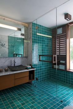 Turquoise almost teal or emerald green shower tile and bathroom floor paired with dark walnut wood vanity. Moody bathroom design.