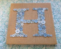 """Burlap backing (white/dark/light tan/medium tan) with light colored buttons in shades of blue, teal, white, grey. For the written """"LOVE"""" squares over the bed."""