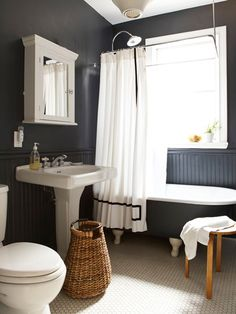 classic hexagon penny tile softens the effect and adds some light, since even the wainscoting is painted black. The clawfoot tub appears to float in space, and the graphic effect is emphasized by the shower curtain.