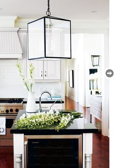 white subway-tile backsplash, a gooseneck faucet, a hanging lantern and stainless-steel hardware