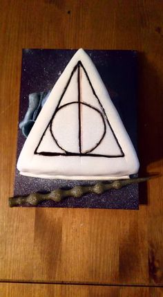 Harry Potter Deathly Hallows cake by The Caking Fairy with Deathly Hallows symbol, Elder wand, Invisibility cloak and resurrection stone. Deathly Hallows Symbol, Harry Potter Deathly Hallows, Invisibility Cloak, Celebration Cakes, Wands, Triangle, Fairy, Symbols, Stone