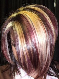 Asymmetrical haircut with highlighted chunks in blonde and red streaks.