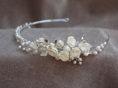This silver plated metal headband is handmade made from fresh water pearls, Swarouski Austrian Crystals, ceramic flowers and leaves.It is put together using jewelry wire to attach the pieces. I can also make this headband with a gold plated metal band instead of the silver. The trim is 9 inches across. The ends have loops to add ribbons to tie in the back. I would be happy to add ribbons at no extra charge upon request.
