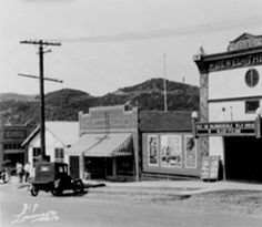 """Exterior view of the Jewel Theathre, the first theatre in Tujunga, 1925. It was built in 1925 and it was located on Commerce Avenue. """"Black Cyclone (1925)"""" starring """"Rex the Unconquerable horse"""" was showing at the time the photograph was taken. The Sweet Shop is located to the right of the theatre. Photographers: J. H. Lamson (no.319) and The Record-Ledger. Donor: The Record-Ledger. Black and white photograph."""