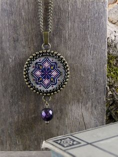 The geometric pattern in this hand-embroidered necklace is cross-stitched on a beige color Murano fabric with threads in magenta pink, navy blue