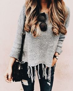 Gray fringed sweater over black distressed jeans.