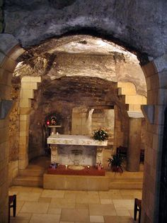 """Basilica of Annunciation. The following photo shows the grotto's interior, with the beautiful 18Th C altar dedicated to the Annunciation (see below). On the right of the altar - an ancient  column, probably placed there in the fourth century to mark the place where the angel appeared. Behind it are stairs that lead up to a small cave (called """"Mary's kitchen"""") and an exit to the yard."""