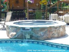 Raised spillover spa with custom stone work around the spa, spilling into this custom vinyl liner pool.