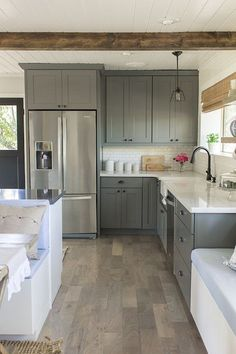 gray and white kitchen, white wood floors, gray cabinets, wood beams, modern farmhouse