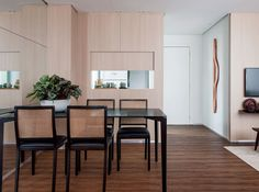 Com uma porta deslizante de carvalho-ibiza, o passa-pratos pode ficar escondido quando não estiver em uso. Na hora das refeições, basta levantá-la. Mesa e cadeiras de jantar da São Romão. A escultura pendurada na parede é de Chico Baumecker (AM Galeria de Arte).