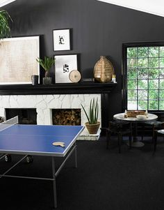"When you walk into that room in the daytime, your eye goes straight outside. Black stretches the perimeter. With black walls and a black carpet, everything floats and the room seems boundless,"" says designer Windsor Smith. She chose to create a game room rather than a formal living room in her Los Angeles family home."