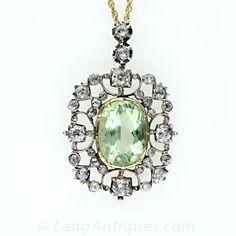 A gorgeous 5.15 carat light yellowish green beryl (the same material as emerald, but a lighter hue) is framed by an openwork scroll motif se...